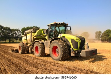 PACOV, CZECH REPUBLIC - August 15, 2015: Big slurry injector releasing liquid manure and tilling field before spring sowing of potatoes, frontal perspective. blue sky in the background, heavy weight