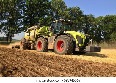 PACOV, CZECH REPUBLIC - August 15, 2015: Big Claas Xerion tractor on headland while injecting slurry into field with wheat stubble, big tyres, new tread, tilled soil in the foreground, blue sky