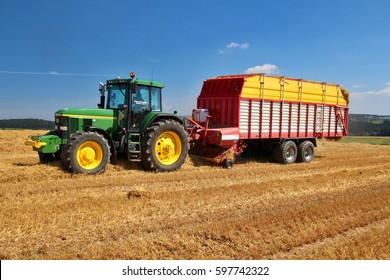 PACOV, CZECH REPUBLIC - August 15, 2015: Self loading wagon attached to green tractor, picking up and transporting straw, bedding for cows, grain harvest, conventional agriculture, side perspective
