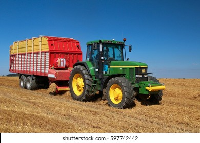 PACOV, CZECH REPUBLIC - August 15, 2015: Green tractor on field with barley stubble picking up straw for feeding cows, blue sky on background, frontal perspective, field certified as bio agriculture