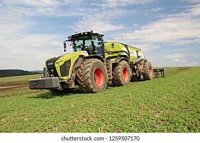 Pacov, Czech Republic - August 29, 2014: Huge tractor Claas Xerion with slurry tank, carting and injecting digestate, end of summer, canola stubble in the foreground