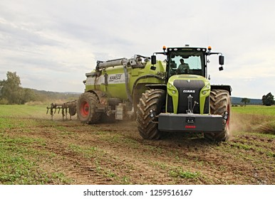 Pacov, Czech Republic, August 29, 2014: Massice tractor Claas Xerion with slurry tank turning on headland, transport and injection of liquid manure, dust, frontal perspective, oilseed stubble