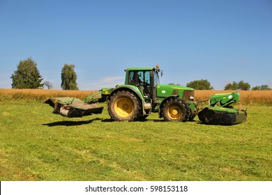PACOV, CZECH REPUBLIC - August 5, 2015: John Deere tractor with mower while cutting grass for cattle, turning on headland, header lifted up, blue sky and rape field in the background, green machinery