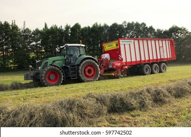 PACOV, CZECH REPUBLIC - August 7, 2013: Dried grass from small mountain meadow being loaded into wagon attached to green tractor, used for feeding cows and pigs, bio agriculture, heavy machinery