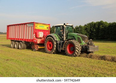 PACOV, CZECH REPUBLIC - August 7, 2013: Dried grass from small mountain meadow being loaded into wagon attached to green tractor, used for feeding cows bio agriculture, frontal perspective