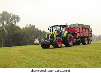Pacov, Czech Republic, September 13, 2014: Graas silage with huge Claas tractor and red trailer, chopped silage transport, forage harvester in background, small meadow