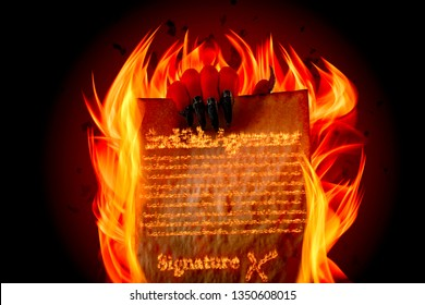 Pact to sell your soul to Lucifer, strike a Faustian bargain or deal with the devil concept theme with Satan holding in creepy ugly red hand with claws burning scroll with fiery text written in flames