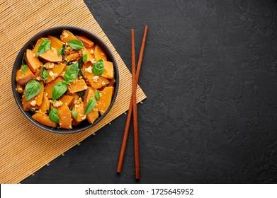 Pad Faktong or Thai Stir-fried Pumpkin in black bowl at dark slate backdrop. Pad Phuk Tong is thailand cuisine dish with sliced Kabocha Squash, eggs or tofu and basil. Thai Food. Top view. Copy space