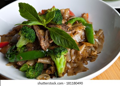 Pad kee mao drunken noodle thai dish closeup with beef and mixed vegetables.
