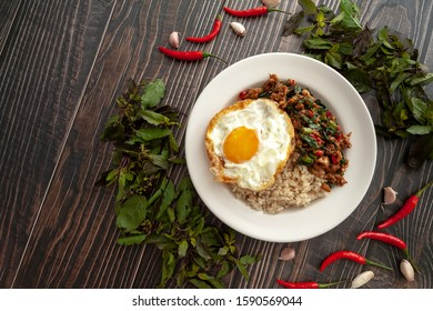 Pad Kra Pao Moo Sab with Kai Dao on wooden backgound, Thai famous food, the stir-fried minced pork, garlic, basil and chili topped with fried egg. This is hot and spicy. Used in menu for restaurant.