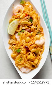 Pad thai noodles with chicken, prawns, mixed greens, chopped peanuts, shallots & lime wedge