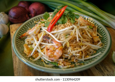 Pad Thai, Thai noodles with shrimps. Thai food Popular with prop all herb and vegetable on wood and green fabric background