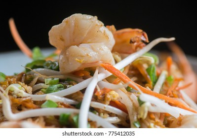 Pad Thai with shrimp, rice noodles, eggs, white radish, sliced carrots, fish sauce, soybeans sprouts with tamarind sauce is shown in a serving bowl.