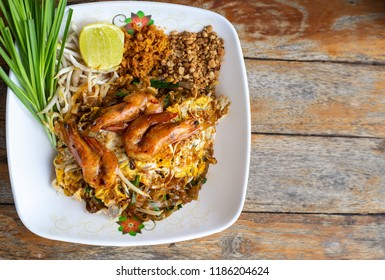 Pad Thai Shrimp in white plate on wooden floor, Thai food