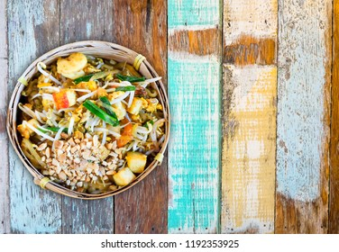 Pad Thai; stir fried noodle signature dish of Thai food, ingredient of noodle, tofu, shrimp, bean sprout, nut and vegetable with sweet and sour taste on wooden background top view with copy space
