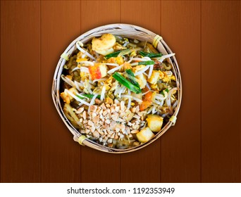 Pad Thai; stir fried noodle signature dish of Thai food, ingredient of noodle, tofu, shrimp, bean sprout, nut and vegetable with sweet and sour taste on wooden background top view