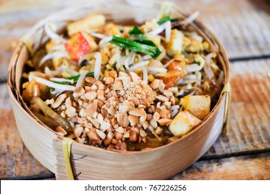 Pad Thai; stir fried noodle signature dish of Thai food, ingredient of noodle, tofu, shrimp, bean sprout, nut and vegetable with sweet and sour taste on wooden background