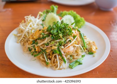 pad thai in white disk on wood table, traditional Thai food, close up.