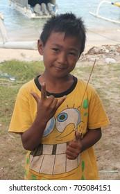 Padang Bai, Bali, Indonesia - 08.11.2017: Young balinese boy in colourful spongebob squarepants shirt smiling friendly.