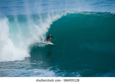 Padang Padang, Bali, Indonesia - September 3, 2013: A surfer is seen here at Padang Padang surf spot riding a wave.