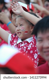 Padang, Singapore / Singapore - August 9, 2005 : A little girl with Singapore flag on her cheek and people around her waving their hands up for cheering on Singapore National Day 2005.