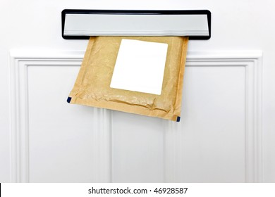 A padded envelope in the letterbox of a white front door, blank label for you to add your own name and address.