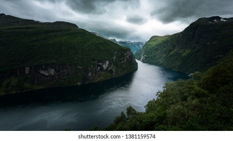 Paddeling with a kayak through the beautiful fjord landscape with high waterfalls to the famous Geiranger Fjord in Norway