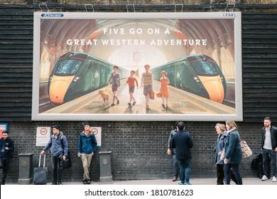 Paddington, London / United Kingdom - March 26, 2018: Londoner smoking under a big advertisement of Great Western Railway outside Paddington train station