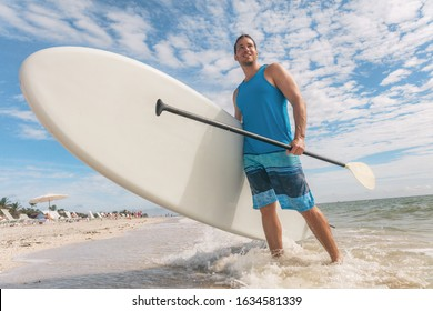 Paddle board fun SUP watersport fitness man carrying paddleboard after water surf session in Sanibel Island, Florida. USA summer travel fit active lifestyle.