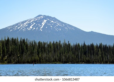 A paddle boarder relaxes in front of Mt Bachelor