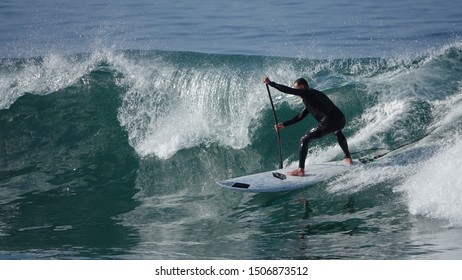 Paddle boarder wearing a full wetsuit surfing a large wave.
