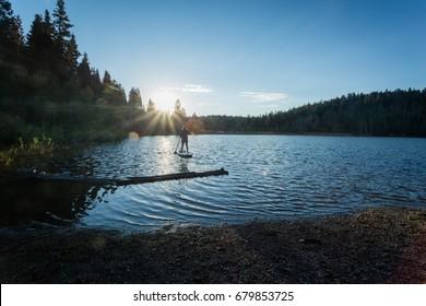 Paddle boarding at sunrise on a mountain lake