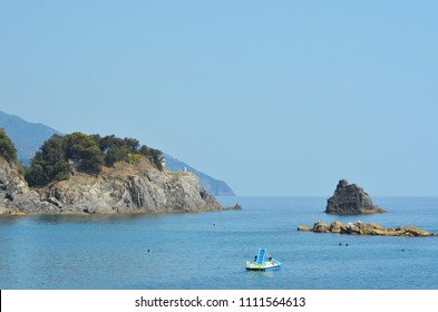 A paddle boat in a bay opening onto the sea. The water is blue and calm, and the sky is clear. A rocky headland is covered with trees, while other rocks are in the water. A few people are swimming.