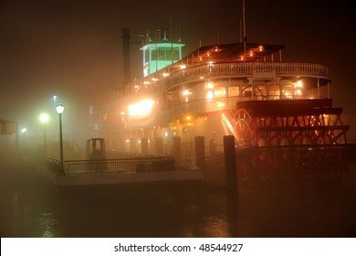 A paddle boat moored on very foggy banks of the Mississippi River in New Orleans, LA