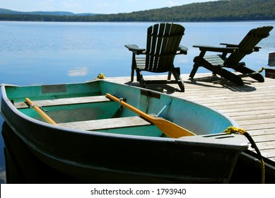 Paddle boat and two adirondack wooden chairs on dock facing a blue lake, shalow DoF.