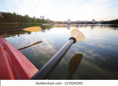 paddle oars close-up on a background of water and cityscape