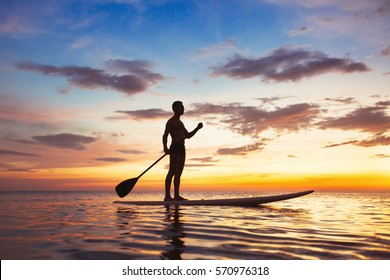paddle standing board, beach leisure activity, beautiful silhouette of man at sunset