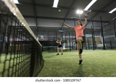 Paddle tennis player woman smashing ball in match while jumping