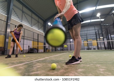 Paddle tennis players collecting balls after training with tube