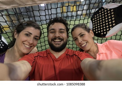 Paddle tennis players taking selfie near to net after match