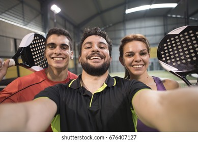 Paddle tennis players taking selfie with camera after macth smiling