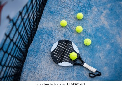 Paddle tennis racket and balls on court artificial grass