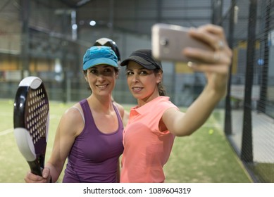 Paddle tennis taking self portrait with phone in court smiling