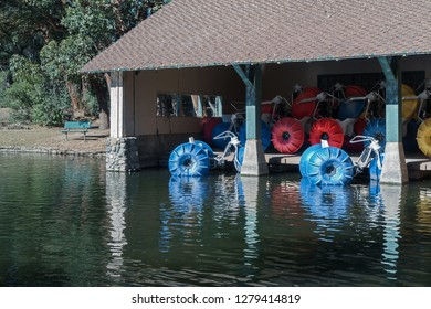 Paddleboats stored under roof of building on lake. Red, blue, and yellow wheels.