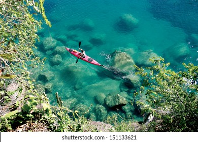 A paddler explores the scenic rock formations of the islands of Lake Malawi, Malawi, Africa, in his kayak.