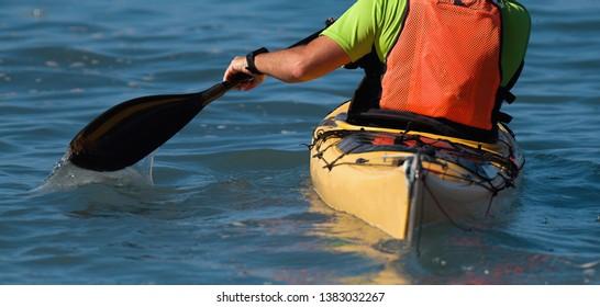 A paddler races his ocean kayak surfski towards the finish