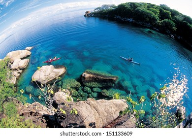 Paddlers explore the scenic rock formations of the islands of Lake Malawi, Malawi, Africa.