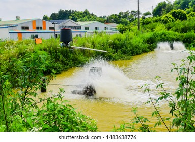 Paddle-wheels being used to aerate pond in front of buildings in rural industrial park. Water is blurry due to motion.