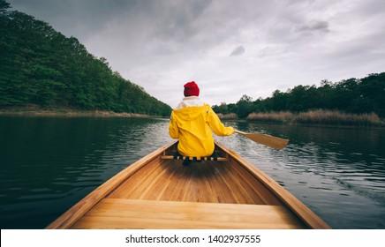 Paddling boat in the rain. Rear view of woman in yellow raincoat paddling canoe. Enjoy canoeing