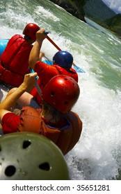 paddling team on a raft and splashing water
